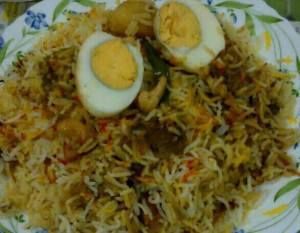 Yummy Biryani with lavish dollops of Ghee and topped with Bolied egg served with Raita