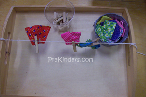 pinning up small dresses on a clothesline with pegs